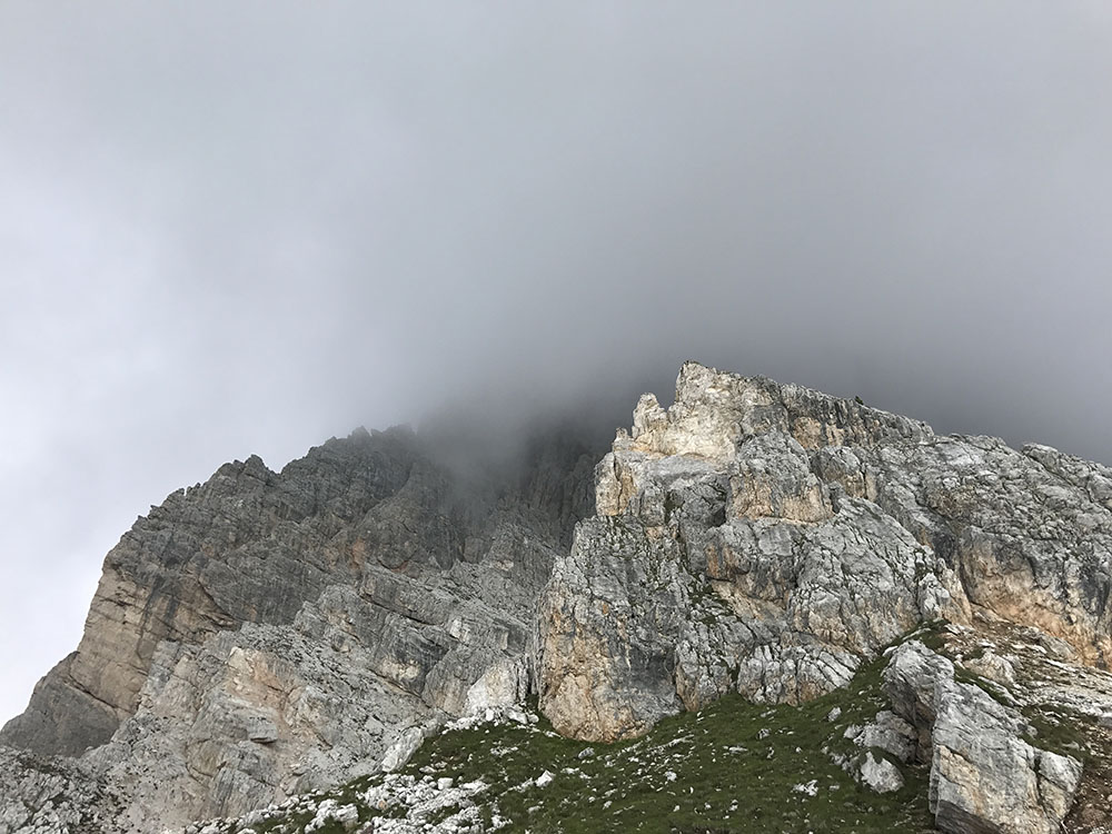 The towering buttress of Punta Anna disappearing into cloud. The ascent route follows the ridgeline.